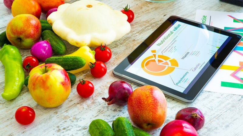 Tablett-PC mit Ernährungs-App auf einem Tisch mit einer bunten Mischung an gesunden Obst- und Gemüsesorten