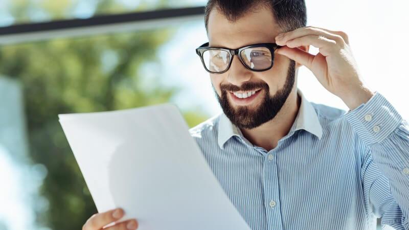 Junger dunkelhaariger Mann mit Brille, Vollbart und gestreiftem Hemd betrachtet glücklich ein Papierdokument