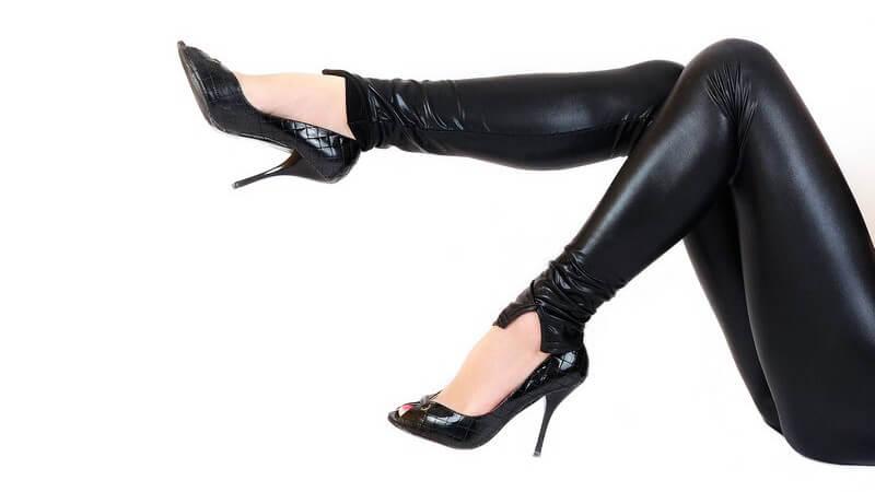 Frauenbeine in schwarzer Latexhose und schwarzen High Heels vor weißem Hintergrund
