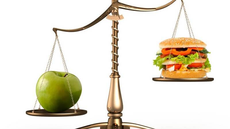 Grüner Apfel und Hamburger auf Waage