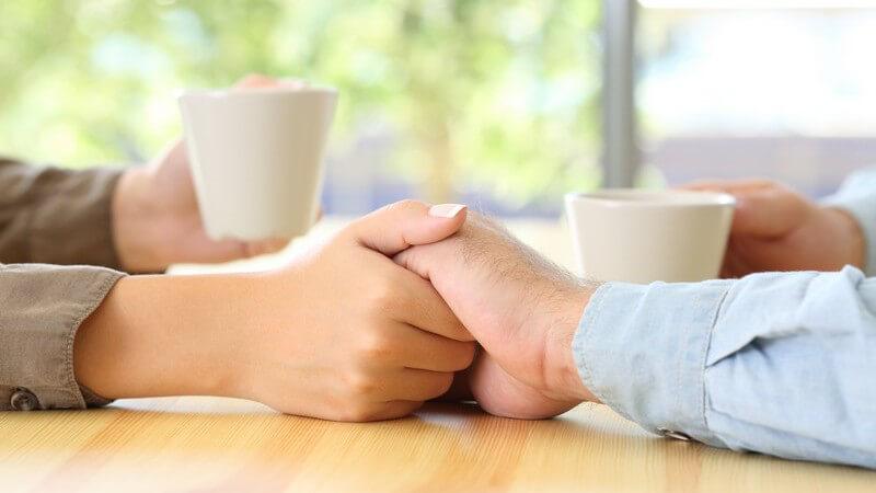 Händchenhaltende Arme eines Paares auf einem Tisch im Cafe, die beiden anderen Arme halten jeweils eine Tasse
