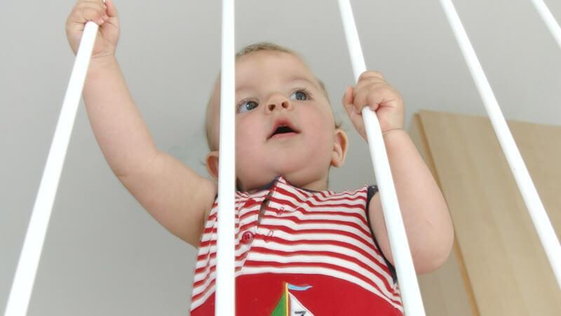 Ansicht von oben: Baby hält sich an Gitter fest, Kindersicherung