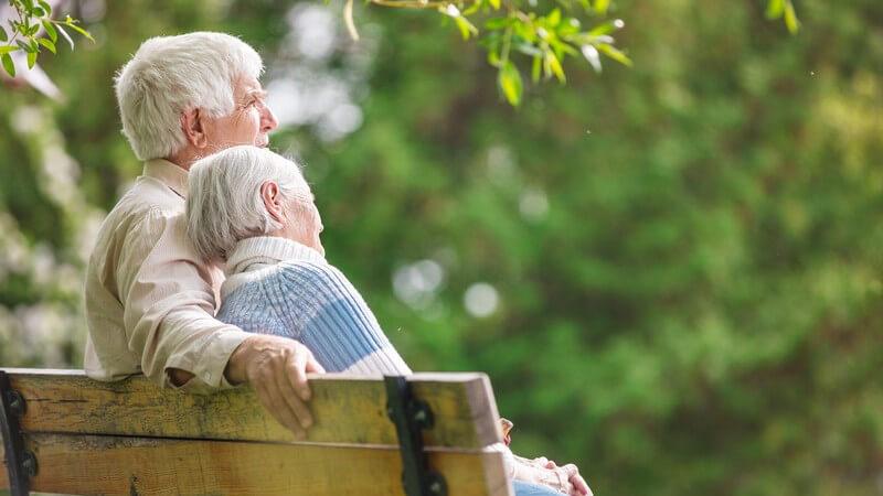 Seniorenpaar mit grauen Haaren sitzt auf einer Parkbank