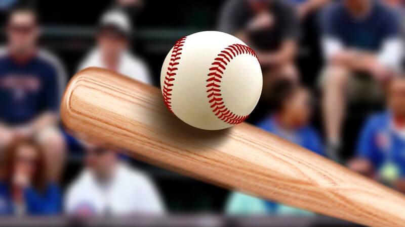 Baseballschläger aus Holz trifft einen Baseball, im Hintergrund Zuschauer