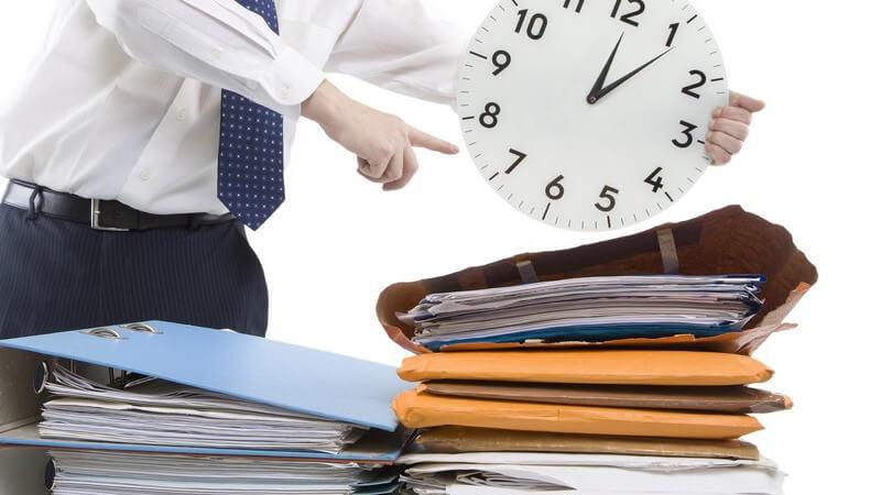 Geschäftsmann hält Uhr über Aktenordner und zeigt darauf, weißer Hintergrund