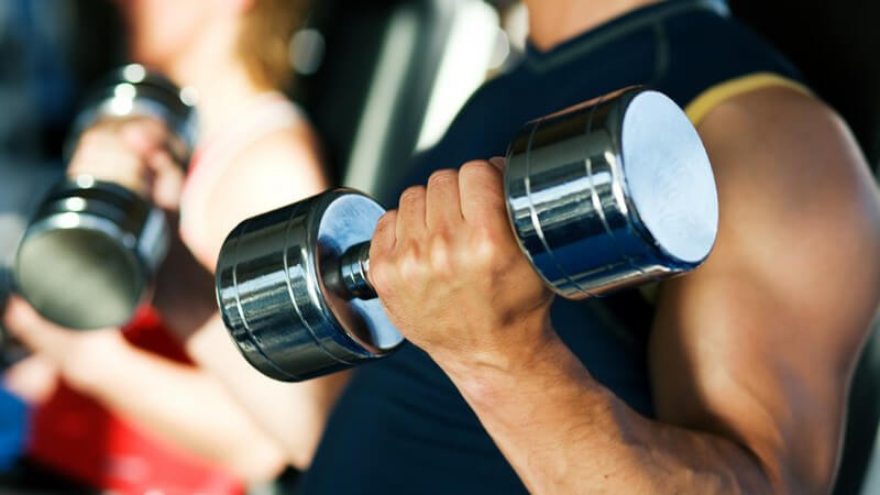 Muskulöser linker Arm mit Kurzhantel