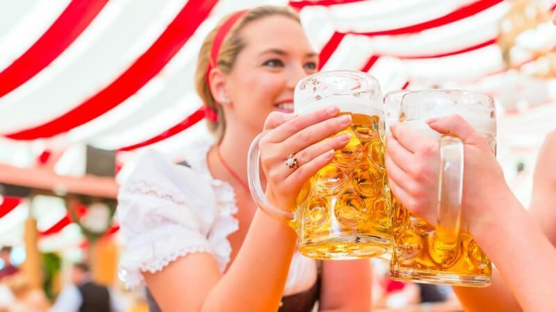 Frauen im Dirndl mit Maß Bier im Zelt des Oktoberfests oder eines Dults