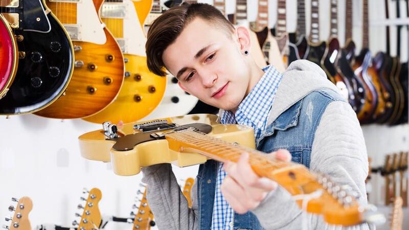 Jugendlicher in blauer Jeansweste begutachtet eine beige E-Gitarre im Gitarrenladen