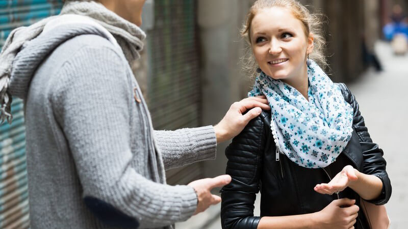 Junger Mann in grauer Strickjacke und Schal spricht eine junge Frau in Lederjacke auf der Straße an