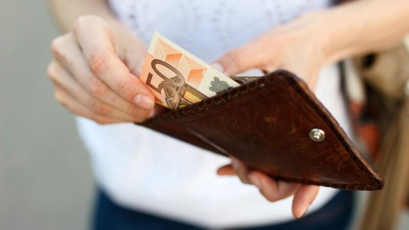 Frau nimmt einen 50-Euro-Schein aus einer braunen Geldbörse aus Leder