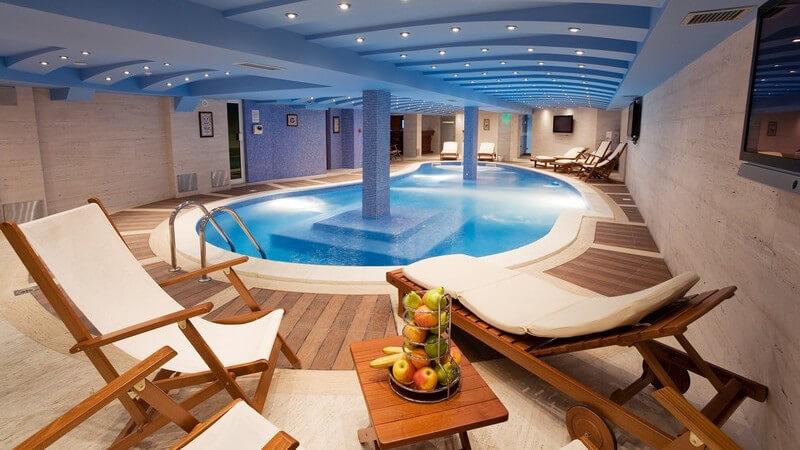 Luxus-Pool mit Liegestühlen aus Holz unter  beleuchteter Decke