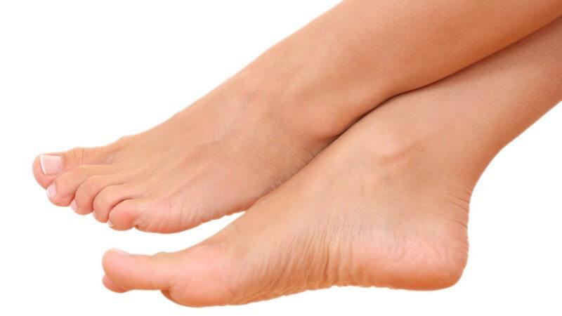 Nackte Füße einer Frau, übereinander geschlagen, auf weißem Hintergrund