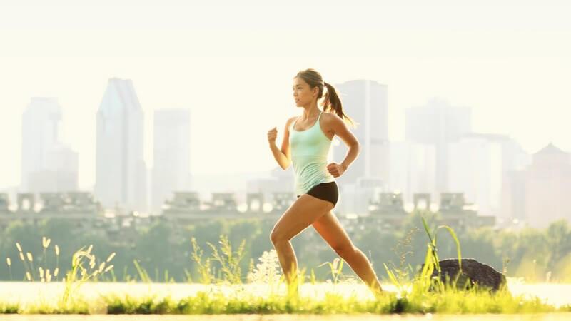 Im Sonnenlicht laufende Frau mit Skyline im Hintergrund