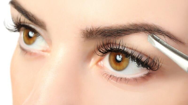 Frau zupft sich die Augenbrauen mit einer Pinzette (Nahaufnahme)