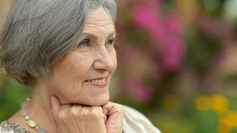 Ältere, modisch gekleidete Frau mit grauen Haaren, im Hintergrund Blumen