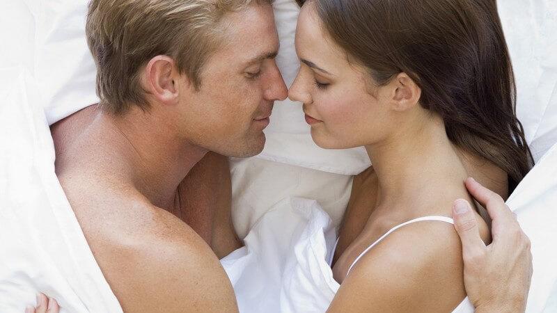 Ansicht von oben, Junges Paar liegt sich zugewandt Arm in Arm im Bett und schläft