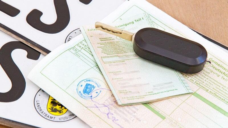 Autoschlüssel, Fahrzeugschein und Fahrzeugbrief liegen auf KFZ-Kennzeichen