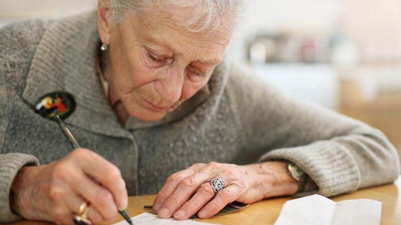Alte Frau sitzt am Schreibtisch und schreibt