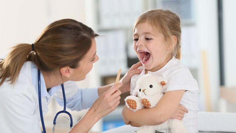 Ärztin untersucht mit einem Holzstäbchen den Rachen eines kleinen Mädchens mit Kuscheltier im Arm
