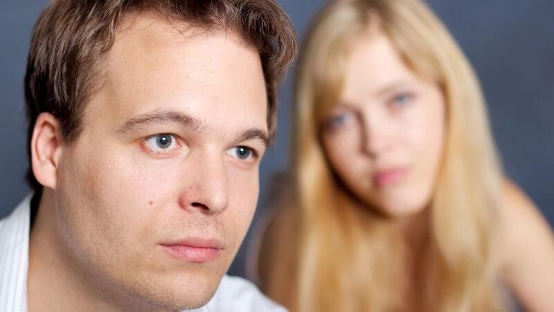 Vorne dunkelhaariger junger Mann in Hemd mit traurigem Blick, hinten blonde junge Frau mit erwartungsvollem Blick