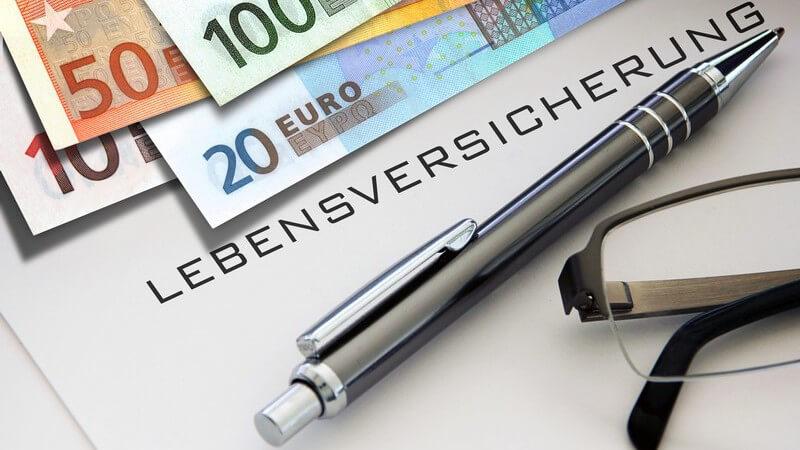 """Euro-Geldscheine, Kugelschreiber und Brille liegen auf einem Blatt mit der Aufschrift """"Lebensversicherung"""""""
