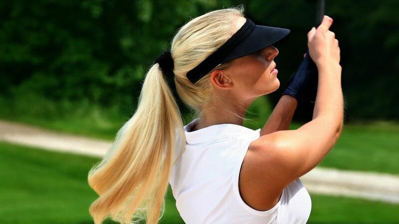 Blonde Frau im Golfoutfit auf Golfplatz