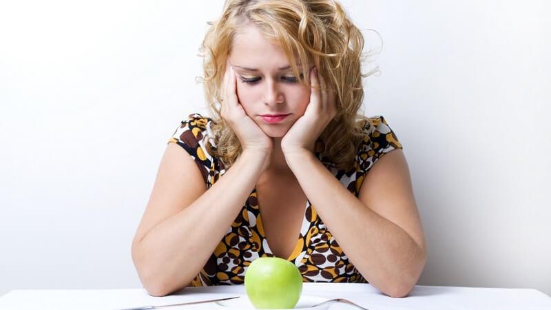 Frau sitzt unglücklich am Tisch vor Teller mit grünem Apfel zur Diät