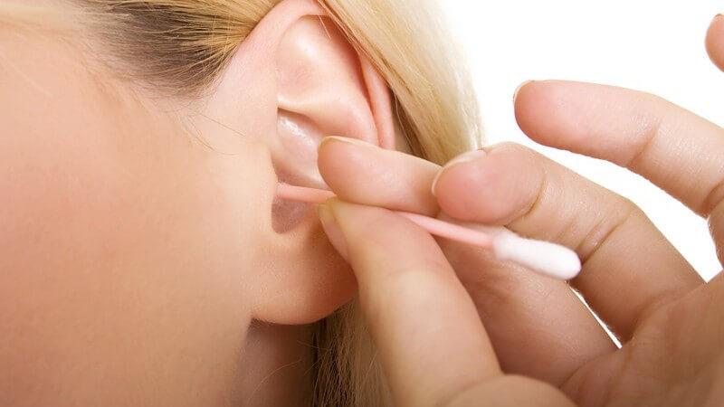 Nahaufnahme blonde Frau putzt mit Wattestäbchen linkes Ohr