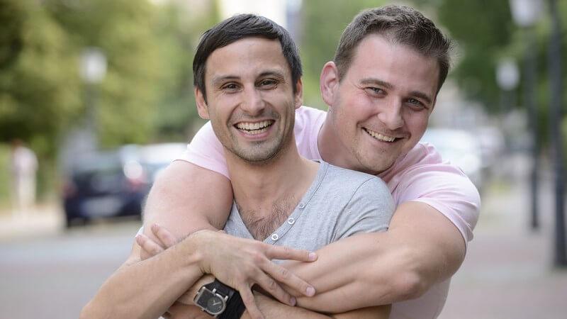 Glückliches Schwulenpaar umklammert auf einer Straße