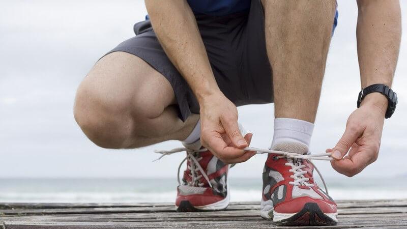 Läufer hockt und bindet seine Laufschuhe