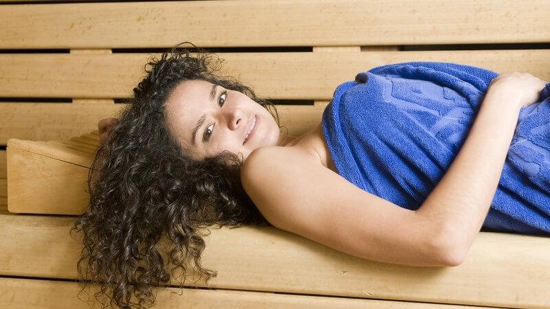 Junge Frau in blauem Handtuch liegt in Sauna und entspannt