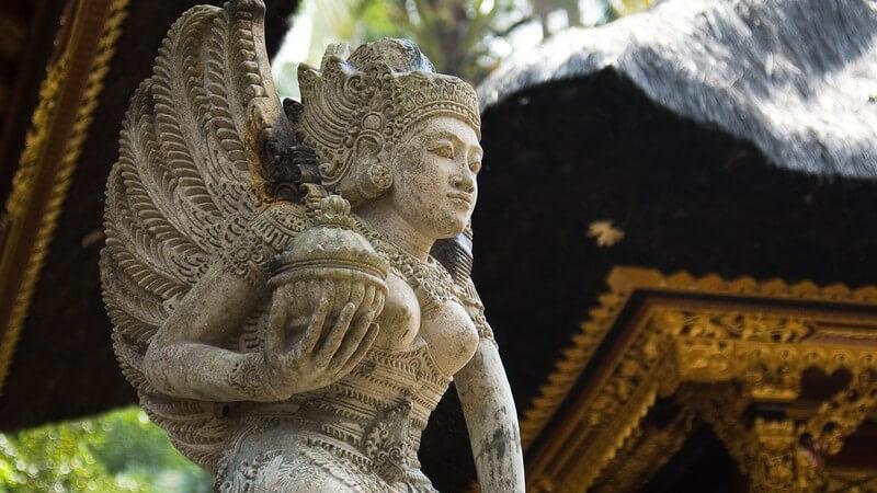 Graue Tempelfigur aus Stein, im Hintergrund Tempel im Buddha Stil
