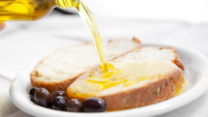 Weißbrotscheiben liegen neben dunklen Oliven auf einem Teller und werden mit Olivenöl übergossen