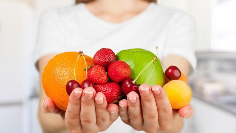 Frau in Küche hält diverse Früchte in den Händen (Orange, Apfel, Erdbeeren, Kirschen)