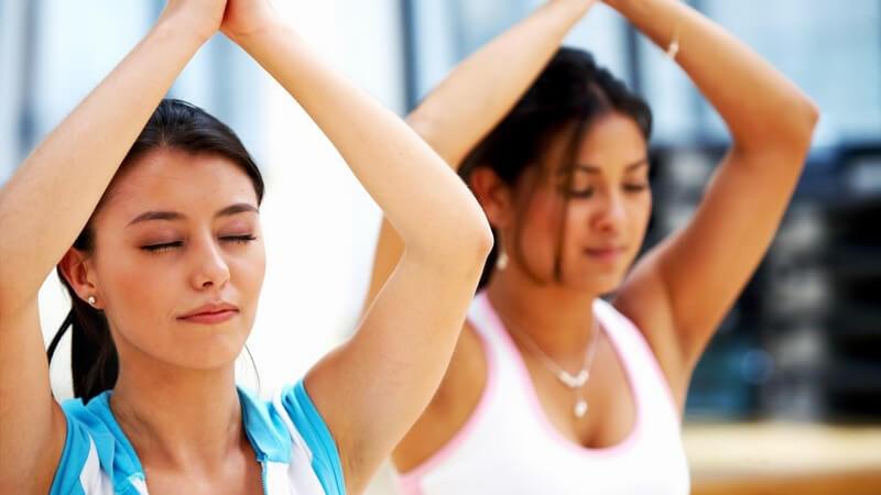 Zwei dunkelhaarige Frauen bei einer Yoga Übung
