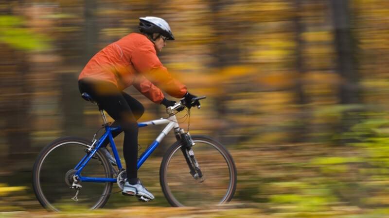 Sportlich angezogene Frau mit Fahrradhelm fährt auf Mountainbike im Wald