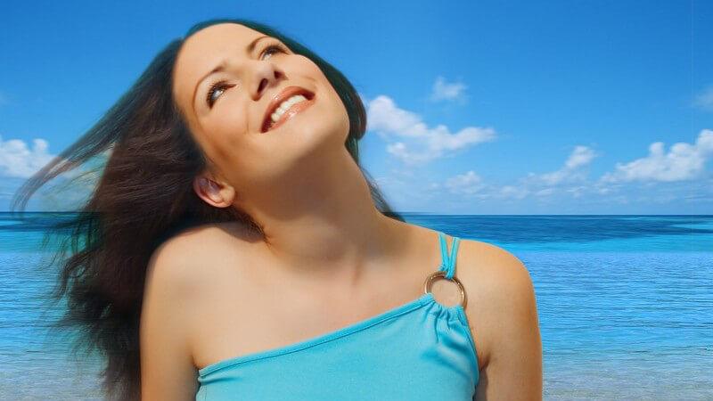 Junge Frau schaut lächelnd nach oben, im Hintergrund Meer