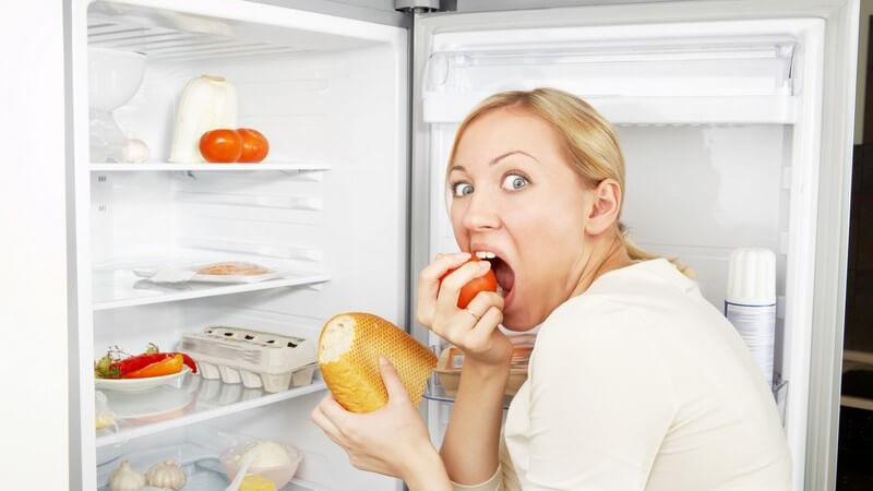 Blonde Frau vor offenem Kühlschrank beisst gierig in Apfel rein