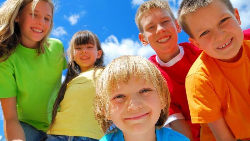 Gruppe von fünf Kindern lächelt in Kamera unter blauem Himmel