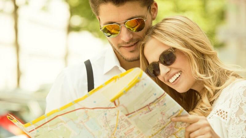 Junges Paar mit Sonnenbrillen sieht sich Stadtplan an, Städtetrip im Sommer