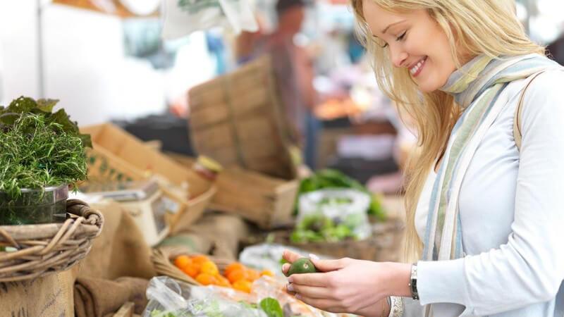 Junge, blonde Frau auf Gemüsemarkt hält Avocado in den Händen