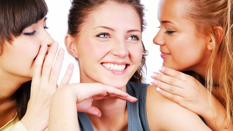 Zwei Frauen flüstern ihrer Freundin etwas ins Ohr