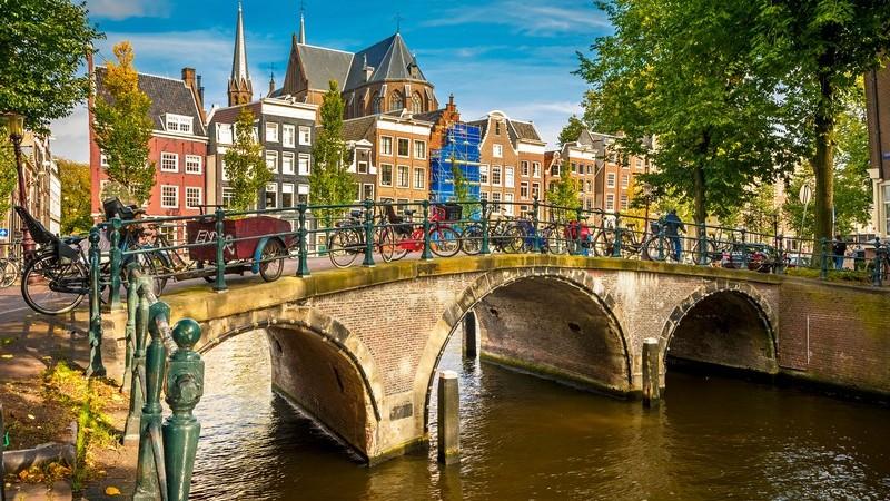 Typisches Stadtbild von Amsterdam, Niederlande: Brücke mit vielen Fahrrädern