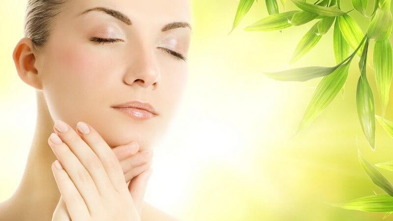 Schöne Frau mit geschlossenen Augen vor einem leuchtend grünen Hintergrund fasst sich mit den Händen ans Kinn