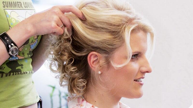 Junge Frau beim Friseur bekommt Hochsteckfrisur für Hochzeit