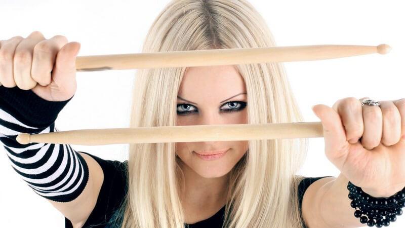 Junge blonde rockige Frau hält Schlagzeugsticks vor die Kamera