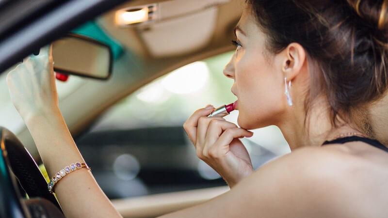Frau schminkt sich die Lippen vor dem Rückspiegel im Auto