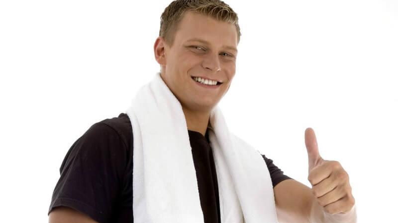 Sportlicher Mann mit schwarzem Shirt und weißem Handtuch zeigt den Daumen nach oben