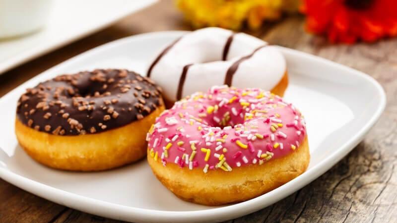 Drei Donuts mit unterschiedlichen Verzierungen auf weißem Teller