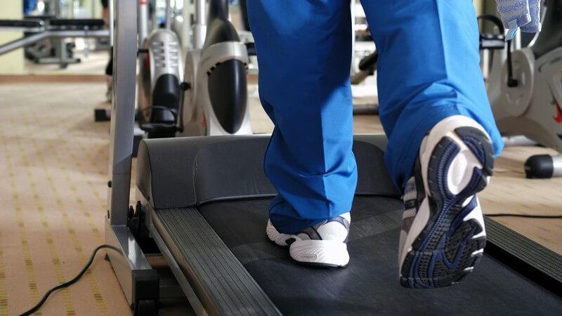 Sportler mit blauer Hose und weißen Laufschuhen auf einem Laufband